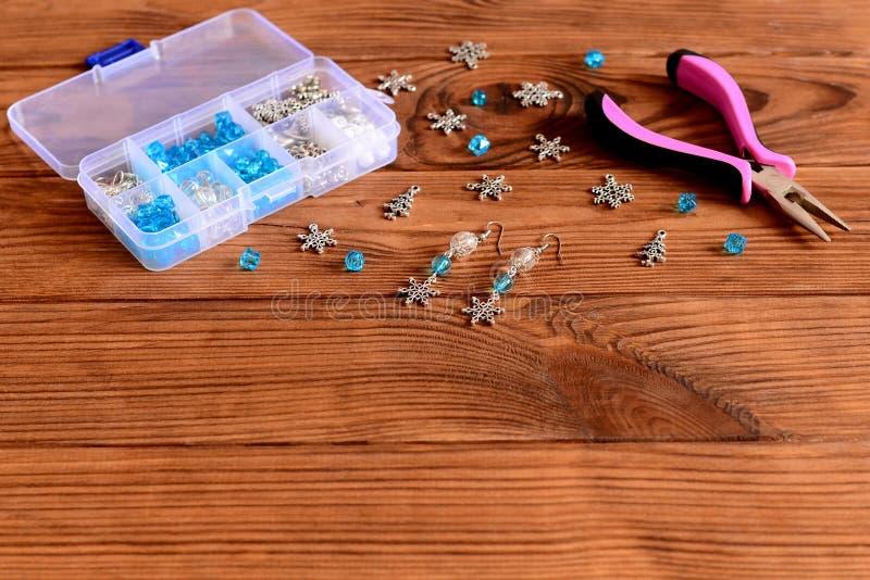 Boucles d'oreille faites main de lustre Boucles d'oreille intéressantes faites de perles bleues et blanches et flocons de neige e image stock