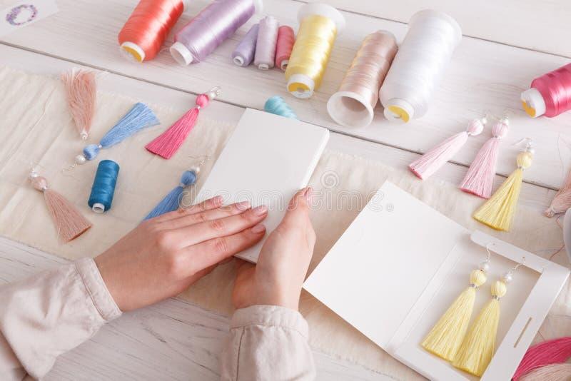 Boucles d'oreille faites main emballant, atelier à la maison photo libre de droits
