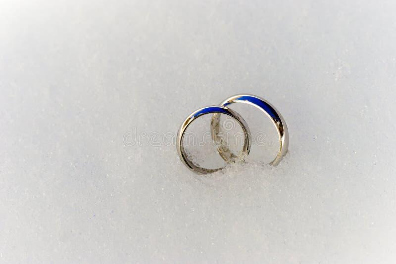 Boucles de mariage dans la neige images stock
