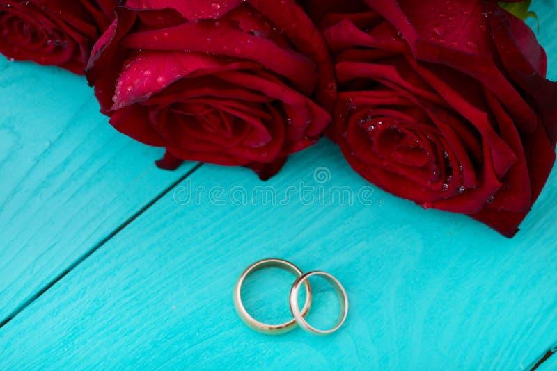 Boucles de mariage et roses rouges Bouquet de mariage sur le fond en bois bleu Foyer sélectif Copiez l'espace Voir les mes autres image libre de droits