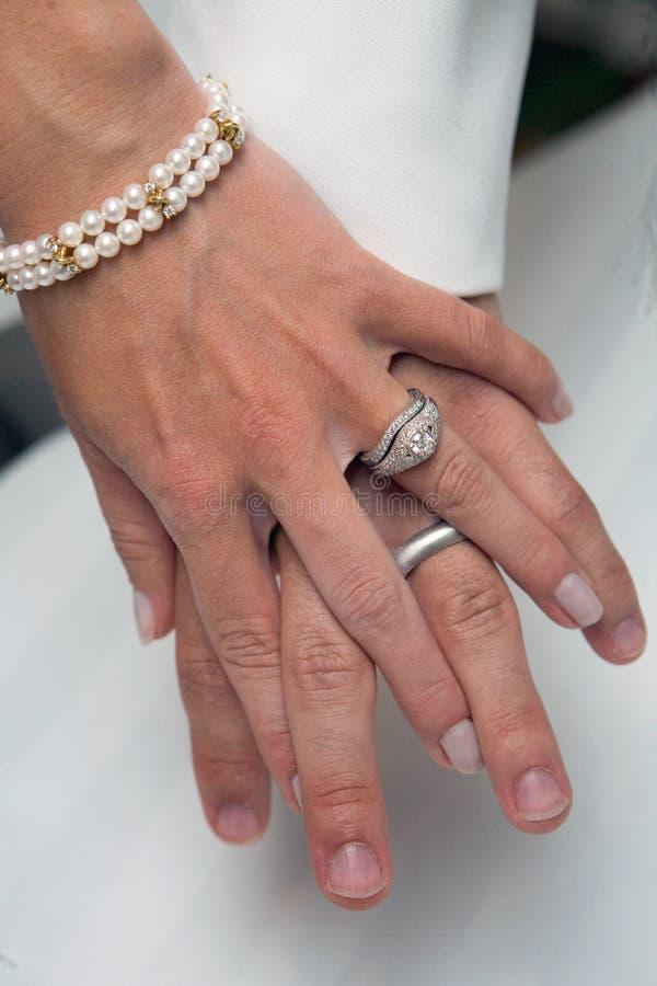 Boucles de mariage, mains de fixation image stock