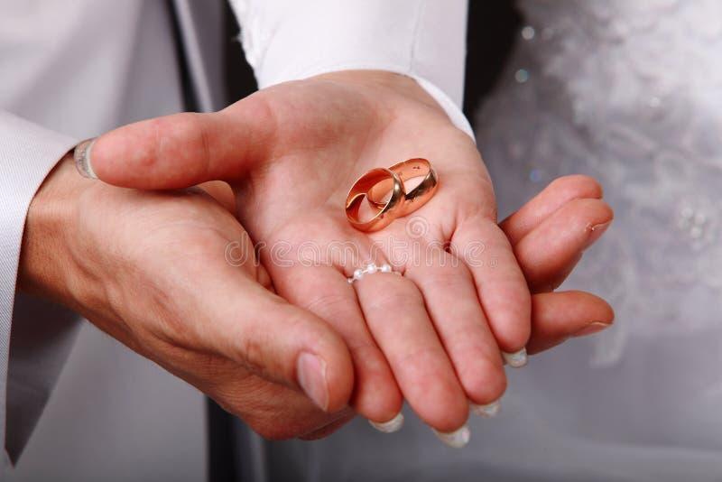 Boucles de mariage sur des mains photos stock