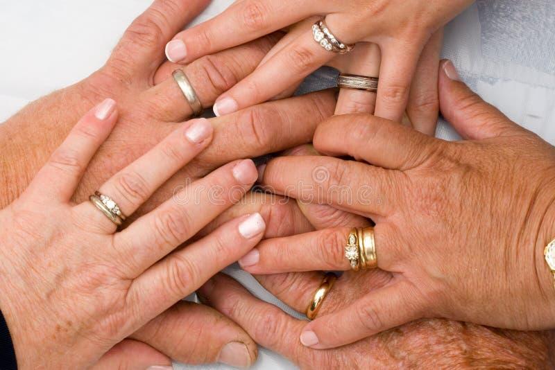 Boucles de mariage sur des mains images libres de droits