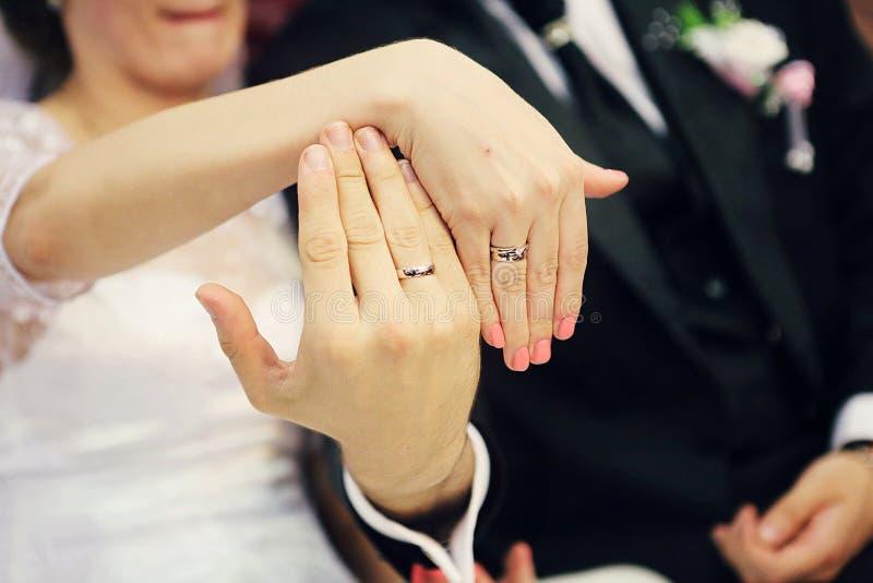 Boucles de mariage sur des mains images stock