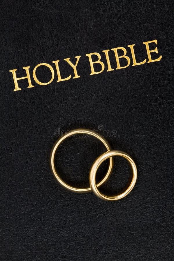 Boucles de mariage sur la bible photographie stock