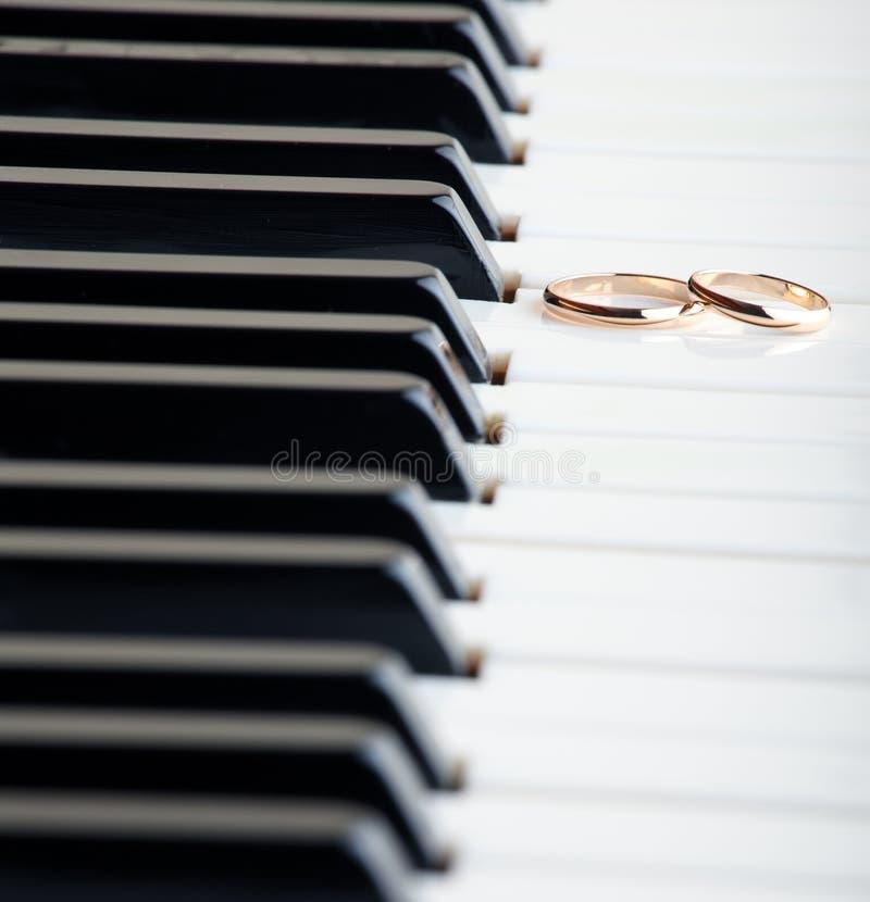 Boucles de mariage sur un piano images libres de droits