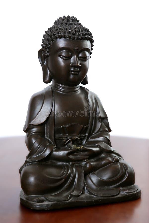 Bouddha peu de sculpture noire au-dessus de bois rouge photographie stock libre de droits