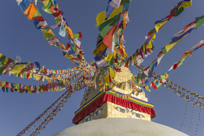 Boudhanath与五颜六色的祷告旗子的西藏佛教Stupa反对一清楚的天空蔚蓝 库存照片