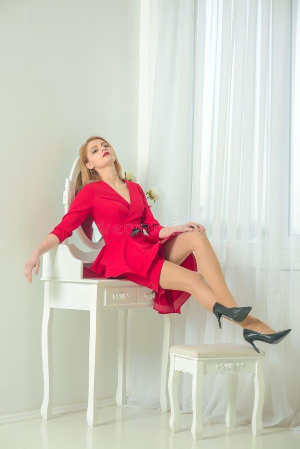 boudoir mulher 'sexy' em seu boudoir Fêmea perfeita a mulher senta-se na tabela do boudoir no quarto branco mobília do boudoir fotos de stock