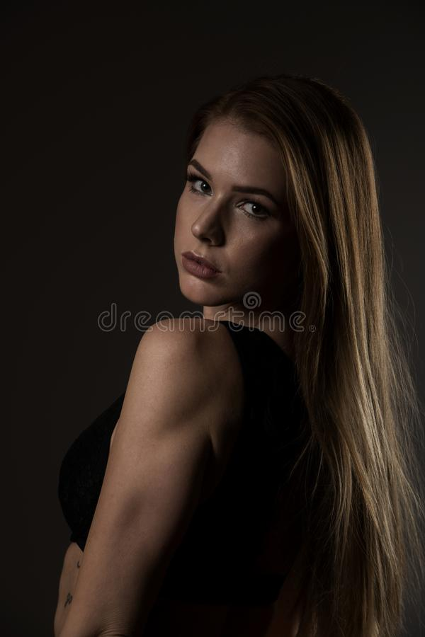 Boudoir photography of a beautiful young woman over dark background stock photography