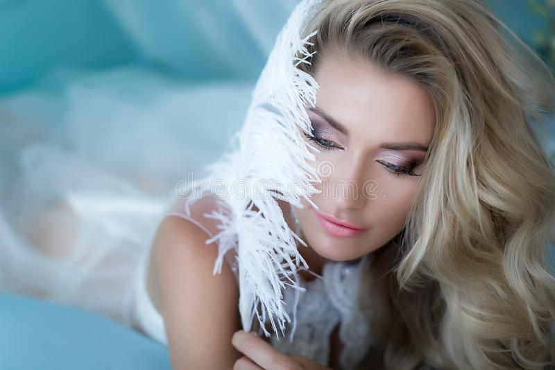 Boudoir photography. Woman blonde with long hair in lingerie on the bed surrounded by flowers tulips. Portrait in the royalty free stock image