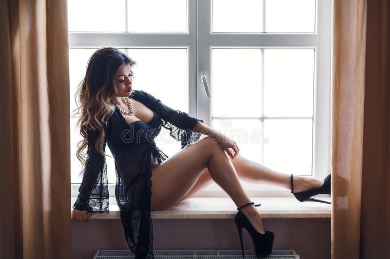 Boudoirfoto des sexy Mädchens die stilvolle schwarze Wäscheunterwäsche tragend, die auf dem Fenster sitzt stockbilder