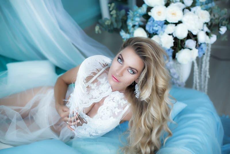 Boudoirfotografie Vrouwenblonde met lang haar in lingerie op het bed dat door bloementulpen wordt omringd Portret in stock foto's