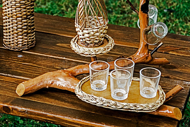 Bough wood wicker tray and glasses. Sitting on a wooden table royalty free stock photos