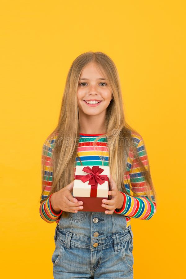 Bought a present. Small child prepare present pack. Little girl smile with wrapped present. Happy kid hold present box. On boxing day. Birthday anniversary royalty free stock photo