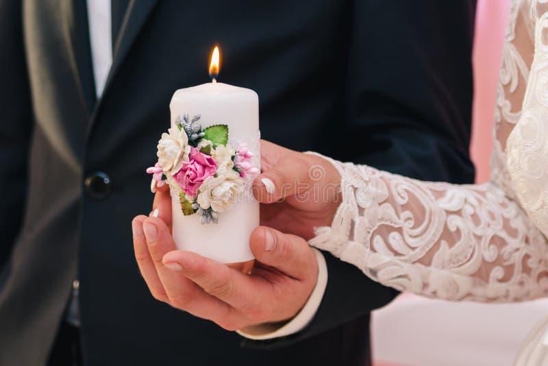 Bougie blanche avec une décoration des fleurs dans les mains des nouveaux mariés Le concept du foyer de famille image stock