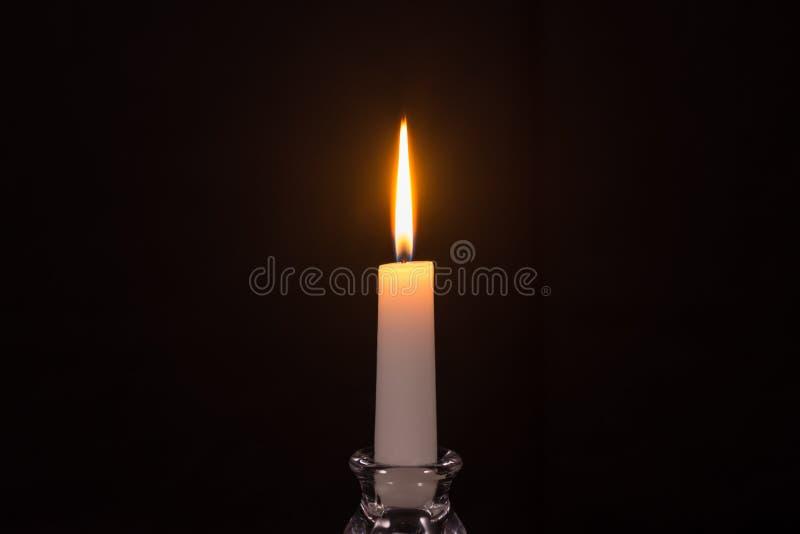 Bougie blanche brûlante sur un fond noir photos libres de droits