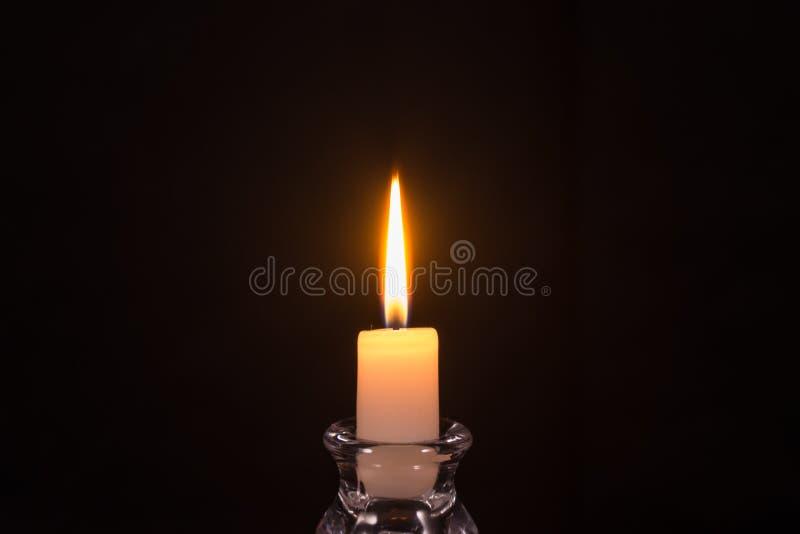 Bougie blanche brûlante sur un fond noir photographie stock