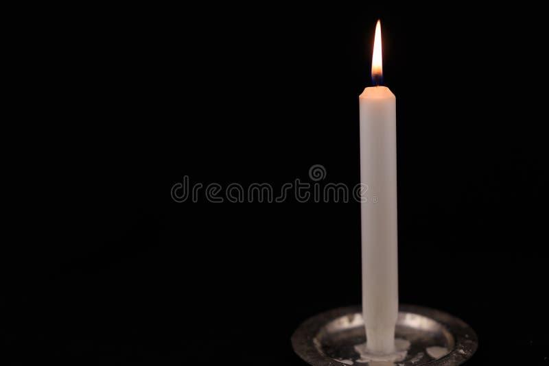 Bougie brûlante blanche sur le fond d'isolement par noir photo stock