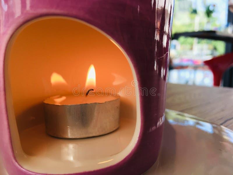 Bougie brûlante du feu dans le pot en céramique image libre de droits