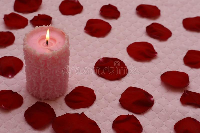 Bougie brûlante et pétales de rose rouges image libre de droits