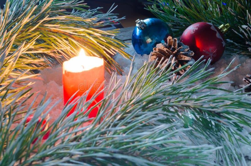 Bougie brûlante sur la neige parmi les branches du sapin et des jouets pour Noël image stock