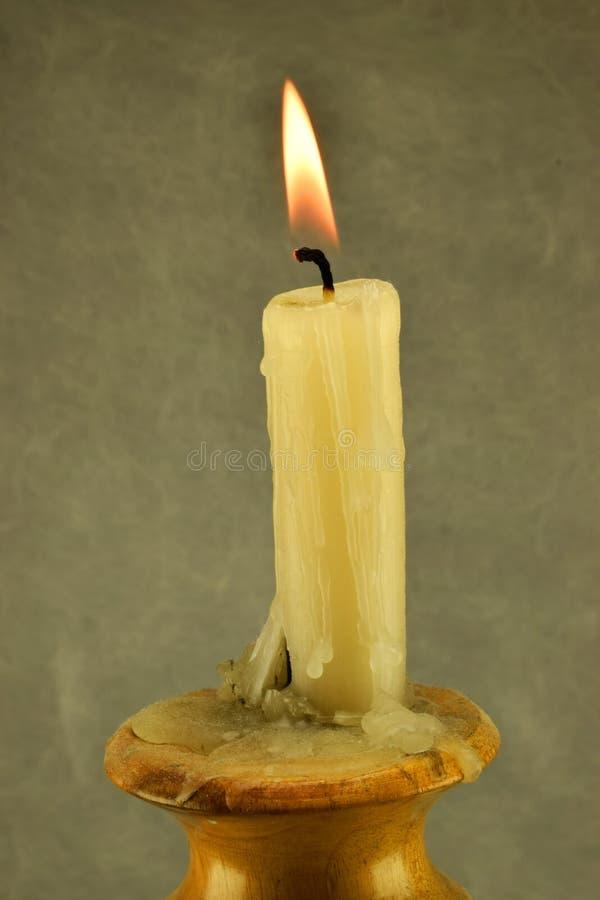 Bougie brûlante sur un chandelier en bois images stock