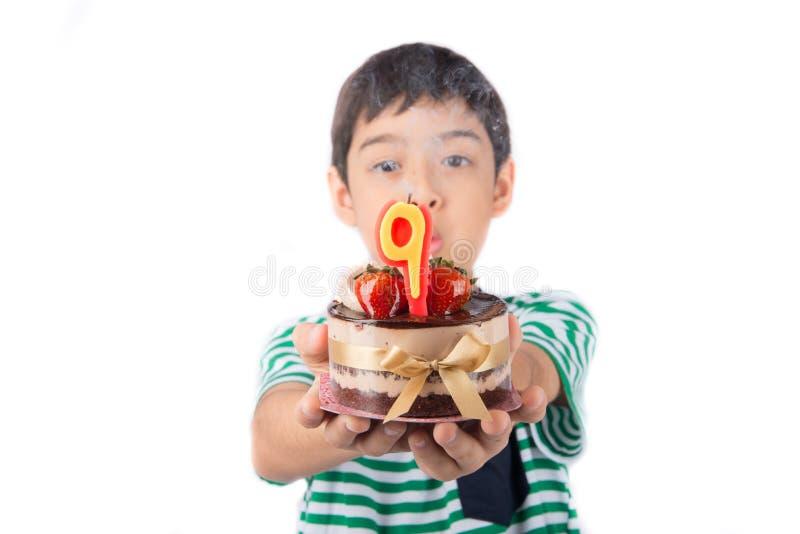 Bougie browing de petit garçon sur le gâteau pour son anniversaire photos stock
