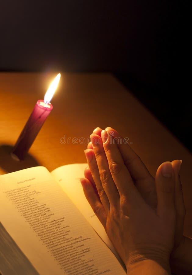 Bougie de bible et mains de prière images stock