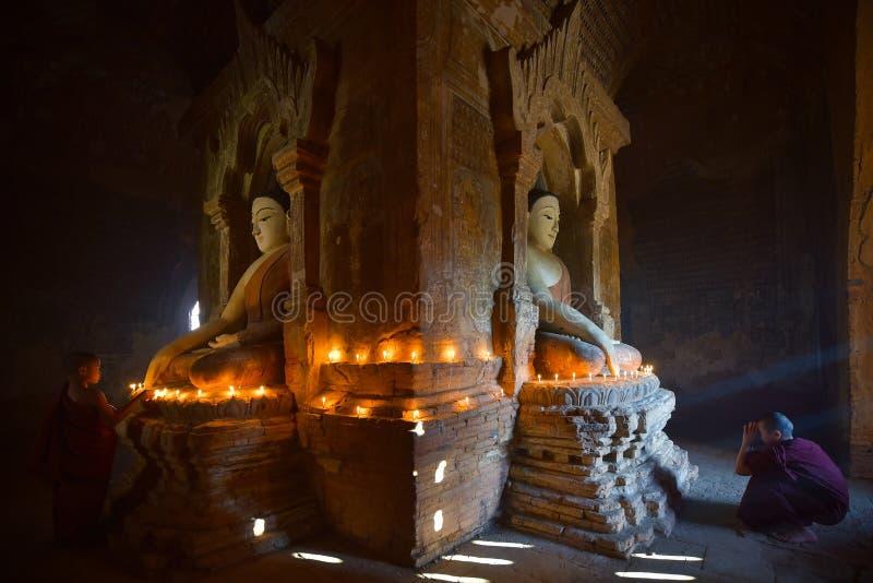Bougie de lumière de deux novices et prier dans la pagoda bagan dans Myanmar photographie stock