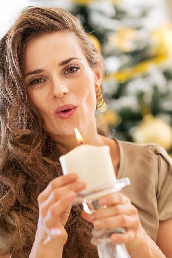 Bougie de soufflement de jeune femme devant l'arbre de Noël image stock