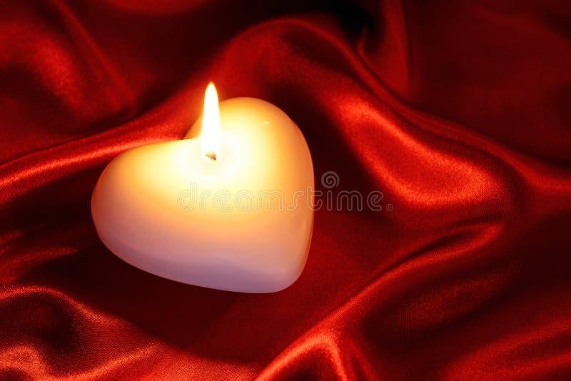 Bougie en forme de coeur sur la soie rouge photo stock