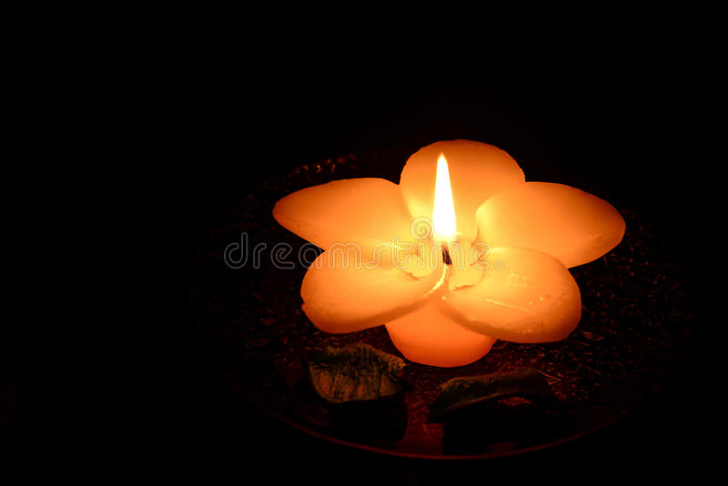 bougie en forme de fleur brûlant sur un fond noir images stock