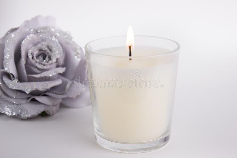 Bougie en verre sur le fond blanc avec une rose, maquette de produit photo stock