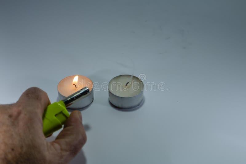 Bougie et feu vert avec la main sur le fond blanc photos stock