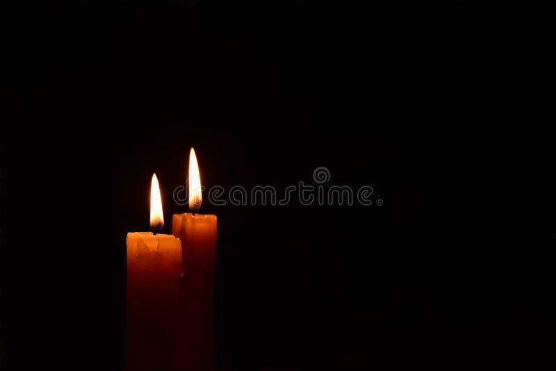 Bougie légère jaune brûlant brillamment à l'arrière-plan noir photographie stock libre de droits