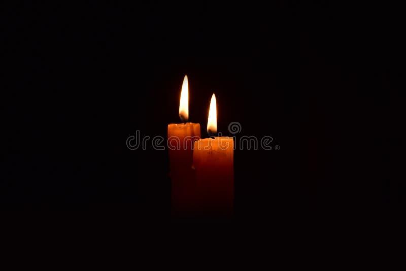 Bougie légère jaune brûlant brillamment à l'arrière-plan noir photo libre de droits