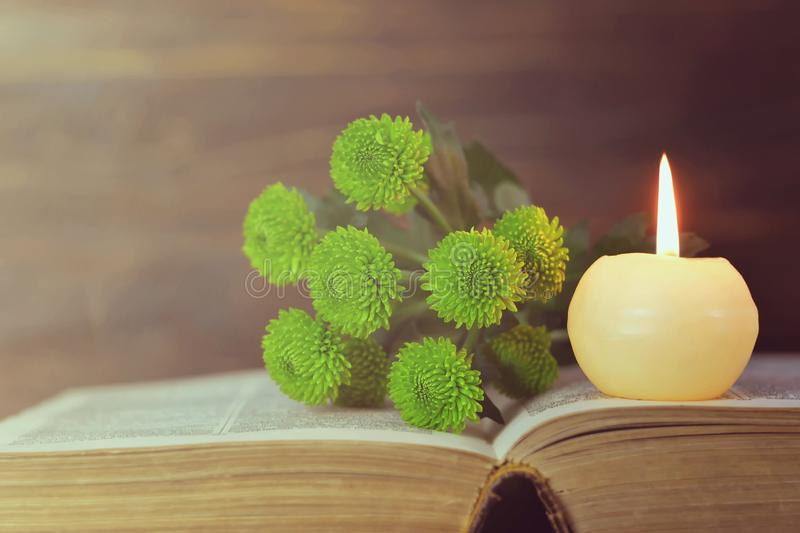 Bougie, livre et fleurs commémoratifs image stock