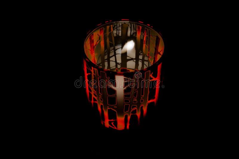 Bougie rampante de Halloween dans le pot rougeoyant rouge avec les branches fantasmagoriques photos stock