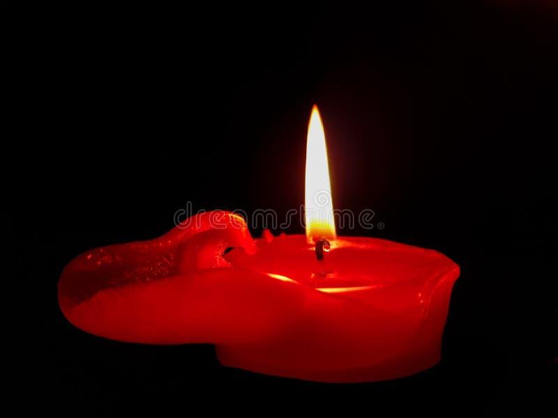 Bougie rouge brûlant dans l'obscurité avec de la cire de débordement image stock