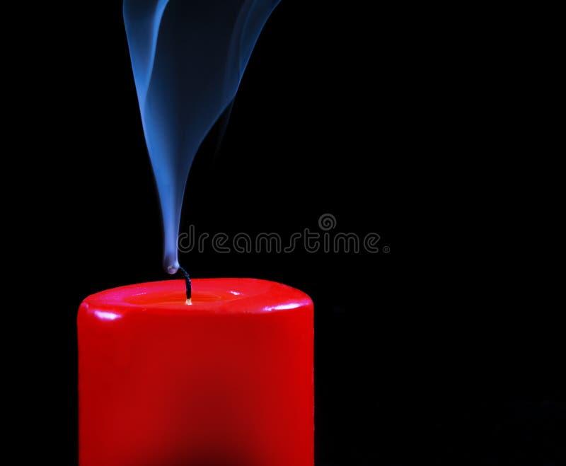 Bougie rouge brûlante avec la flamme de effacement et fumée sur un fond noir photos libres de droits