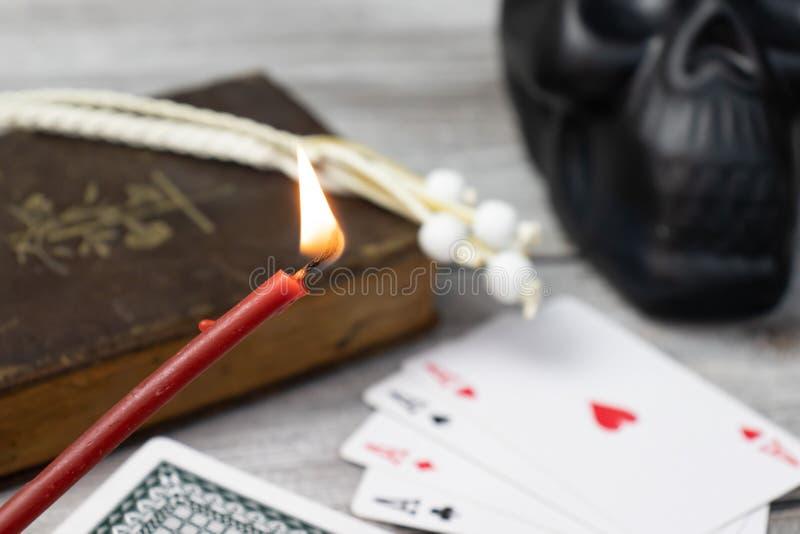 Bougie rouge brûlante d'église dans le foyer, la vieille Sainte Bible brouillée, le crâne noir et les cartes sur la table en bois image libre de droits