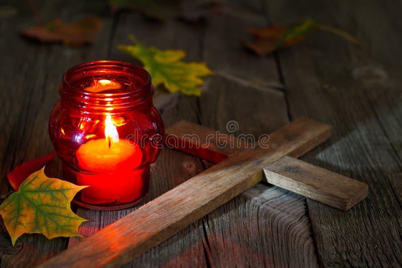 Bougie rouge de lanterne de cimetière avec des feuilles d'automne dans la nuit image stock