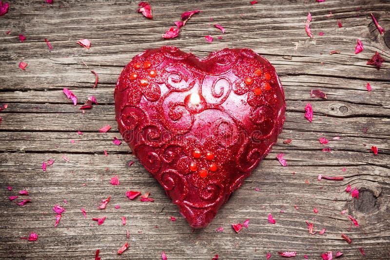Bougie rouge en forme de coeur avec des pétales de fleur sur la vieille table en bois photographie stock libre de droits
