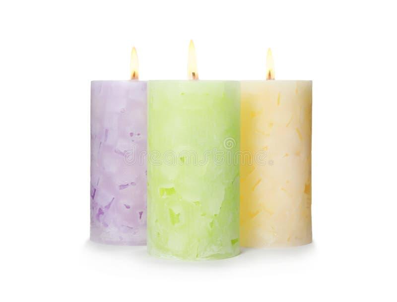 Bougies allumées de cire de couleur sur le blanc photographie stock libre de droits