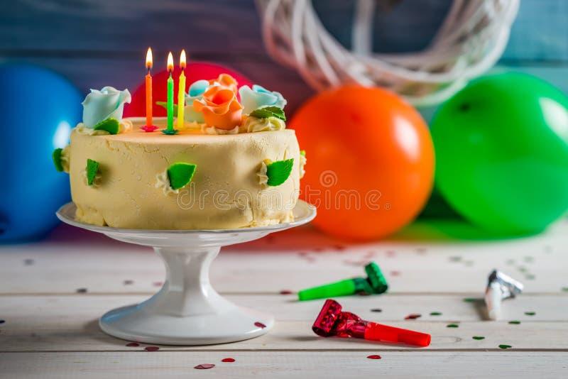 Bougies allumées sur le gâteau d'anniversaire photographie stock libre de droits
