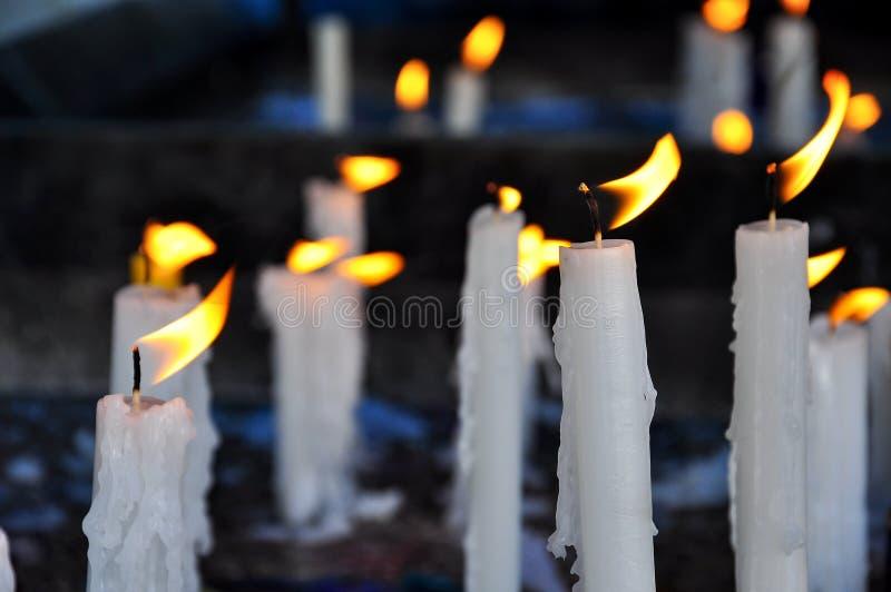 Bougies blanches dans le vent photographie stock libre de droits