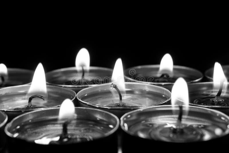 Bougies brûlant à l'arrière-plan noir image stock