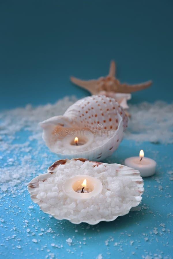 Bougies brûlantes avec des coquillages et sel de mer sur la table de couleur photos libres de droits