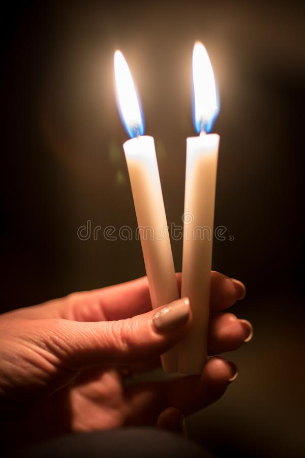 bougies brûlantes d'église dans les mains des enfants sur un fond foncé image libre de droits
